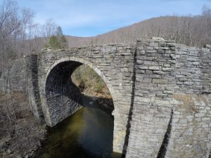 Fisheye image of old stone bridge over a river, with trees and mountains in the background.