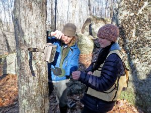 Sally Naser and a volunteer stand by a tree in winter time checking to see if it is set up properly