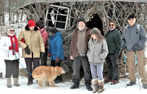 Eight people and a dog pose in front of a structure made from branches and twigs