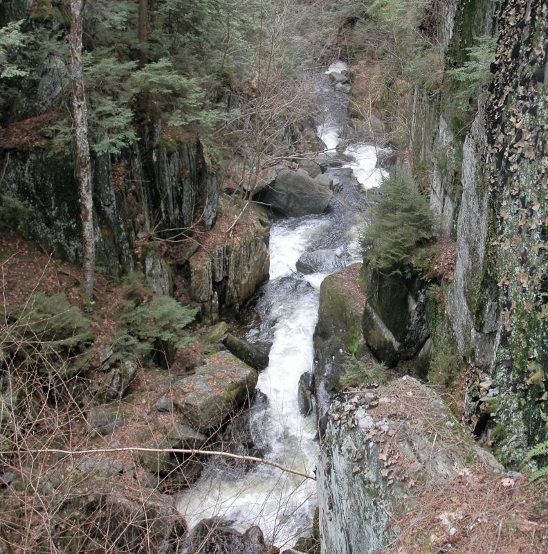 water cascades overs rocks in a river between to rocky cliffs