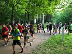 A crowd of runners take off from the starting line on a trail. Green trees are in the background.