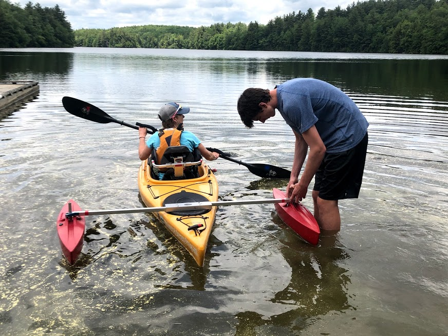 AOA staff preparing kayak on a lake with participant.